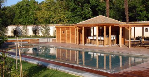 Piscine mirroir devant un bungalow au milieu d'un jardin